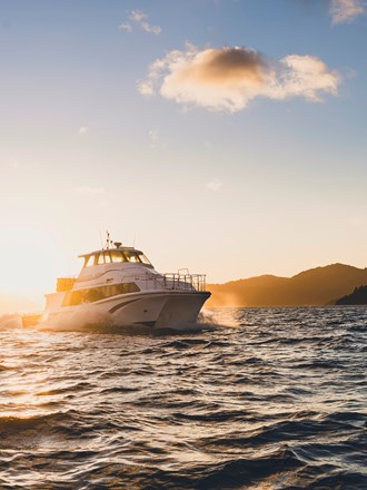 A Cougar Line boat cruises into Queen Charlotte Sound/Tōtaranui while the sun rises behind it in the Marlborough Sounds, New Zealand