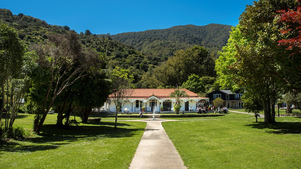 Large sweeping lawns and the front of historic Howden House with its distinctive verandah and orange tiled roof, in the Marlborough Sounds at the top of New Zealand's South Island.