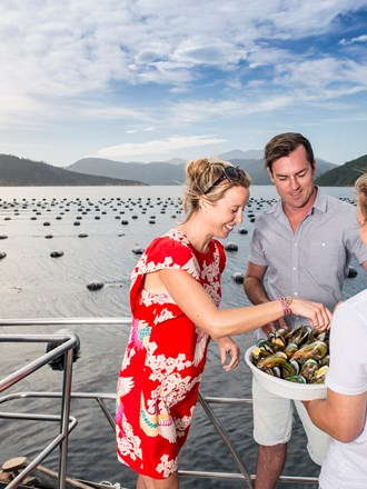A couple sample Greenshell mussels from a Marlborough Tour Co staff member onboard a boat near a mussel farm in the Marlborough Sounds at the top of New Zealand's South Island