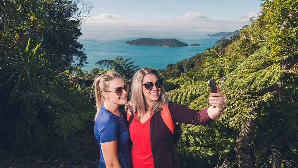 Two women hikers take a selfie photo along Queen Charlotte Track in the Marlborough Sounds, New Zealand, with Motuara Island and sea view in distance.