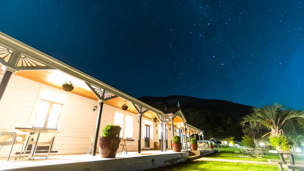 A view at night along the verandah of historic Howden House with lights on and stars in the sky, in the Marlborough Sounds at the top of New Zealand's South Island.