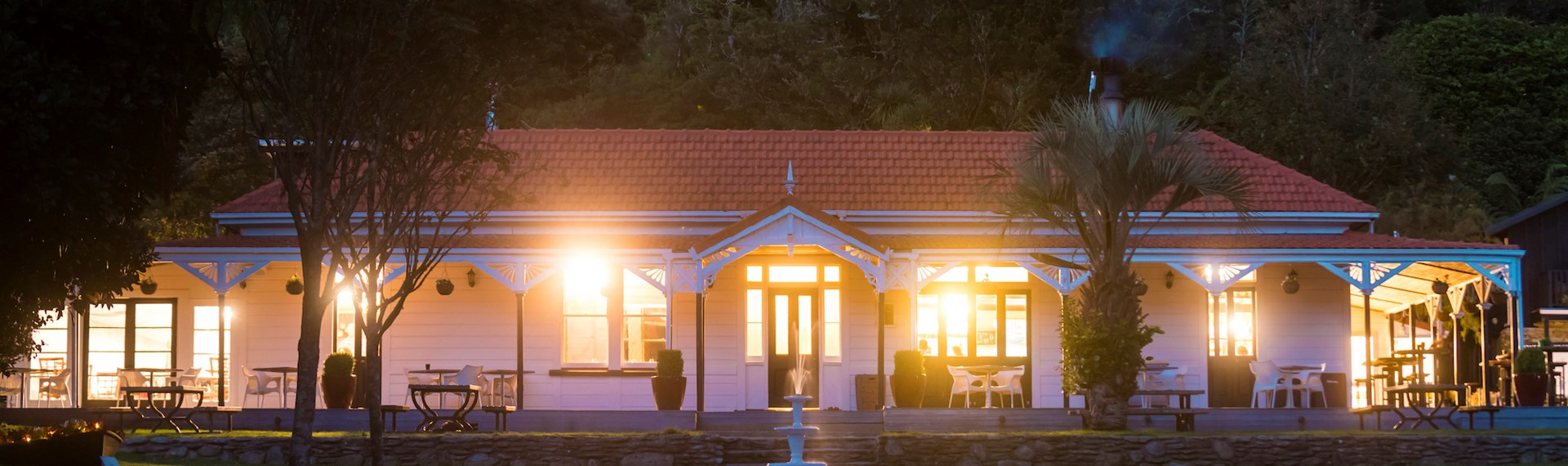 The front of historic Howden House at Furneaux Lodge showing the long verandah and orange tiled roof, in the Marlborough Sounds at the top of New Zealand's South Island.