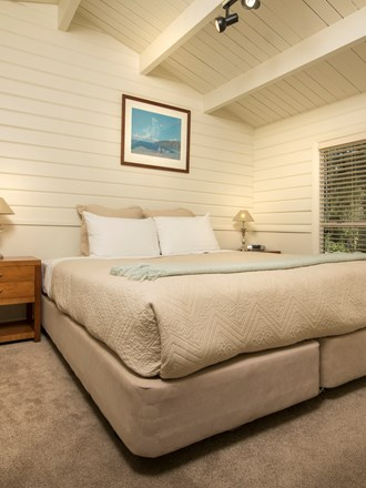 A Cook's Cottage bedroom with a king bed at Furneaux Lodge in the Marlborough Sounds, New Zealand.