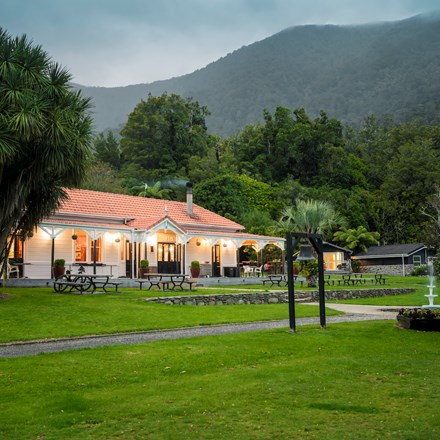 The front of historic Howden House with orange tiled roof and lawn in front, in the Marlborough Sounds at the top of New Zealand's South Island.