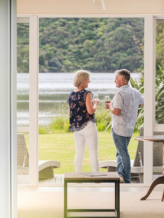 A couple enjoying glasses of Pinot Noir outside on an Endeavour Suite Rows of wine glasses on a shelf at the Furneaux Lodge  in the Marlborough Sounds at the top of New Zealand's South Island.